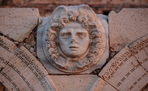 The head of Medusa on a stone arch in the ruins of the forum (Image Source: http://www.telegraph.co.uk/news/worldnews/africaandindianocean/libya/11475388/Leptis-Magna-war-torn-Libyas-forgotten-ancient-Roman-city.html)